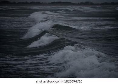 満潮時とシロッコの間に波がビーチに押し寄せる荒れた海の意図的に暗い画像-ヴェネツィア、イタリア