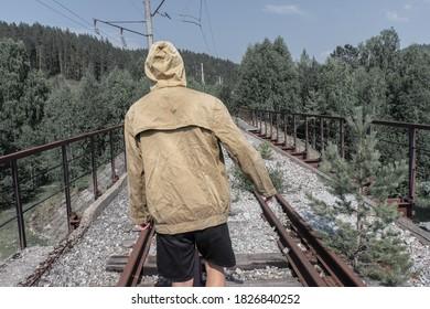 男は廃線となった線路橋を渡って歩きます。道路の向こう側の森の古い鉄橋。