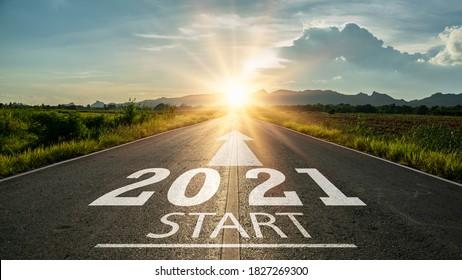 新年2021年またはまっすぐなコンセプトを開始します。日没時にアスファルト道路の真ん中の道路に書かれた単語2021。計画と挑戦またはキャリアパス、ビジネス戦略、機会と変化の概念