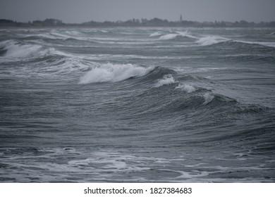イタリア、ベニスの満潮時とシロッコの間に波がビーチに打ち寄せる荒れた海