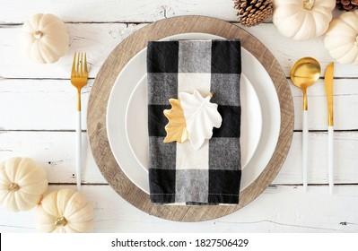 プレート、食器、水牛の格子縞のナプキン、カボチャ、装飾が施された秋の収穫または感謝祭のディナーテーブルの設定。白い木の背景の上面図。