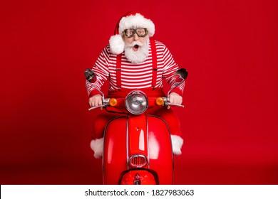 Retrato de su guapo padre de Santa barbudo asombrado impresionado montando ciclomotor entregando regalos tradición viaje velocidad rápida apresuramiento aislado brillante vivo brillo vibrante fondo de color rojo