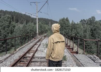 男は廃線となった鉄道橋の上に立っています。道路の向こう側の森の古い鉄橋