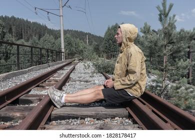 男は廃線の鉄道橋に座っています。道路の向こう側の森の古い鉄の橋。