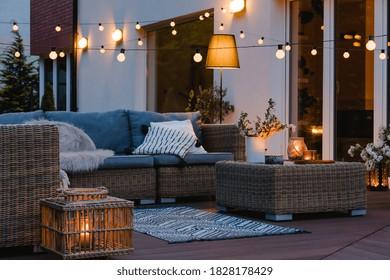 Tarde de verano en el patio de la hermosa casa suburbana con luces en el jardín jardín