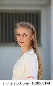 Hermosa mujer rubia con cabello largo trenzado, camisa blanca, ventana con barrotes