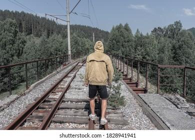 男は廃線となった鉄道橋を渡って歩きます。道路の向こう側の森の古い鉄の橋。