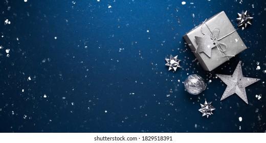 メリークリスマスとハッピーホリデーのグリーティングカード、フレーム、バナー。新年。ノエル。シルバーのクリスマスプレゼント、青い背景の上面図の装飾品。冬の休日のクリスマスのテーマ。フラットレイ。