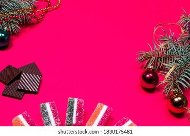 Marmeladni želeji in smrekova vejica s trakom in kroglico na roza ozadju. Novoletna pasica za pecivo s čokoladno sliko s prostorom za besedilo v copyspaceu.