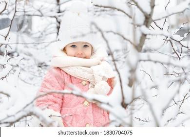 hermosa niña con un abrigo de piel rosa y un gorro de punto entre los árboles cubiertos de nieve. concepto de invierno y navidad