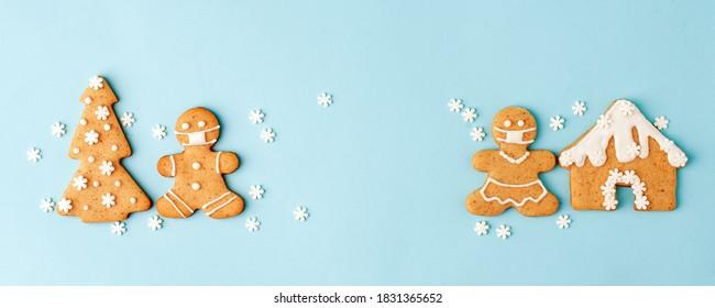 Frohes neues Jahr Satz von Zahlen 2021, Lebkuchenmann in Gesichtsmaske von Ingwerplätzchen glasierte Zuckerglasurdekoration auf blauem Hintergrund, minimales saisonales Pandemie-Winterferienbanner
