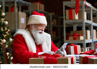 Happy old bearded Santa Claus wearing costume holding cell phone using mobile Christmas promotion sale app on smartphone video calling in virtual online chat sitting at table in workshop on xmas eve.