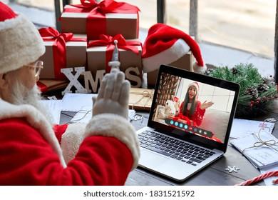 サンタクロースのビデオの肩越しに、ラップトップで子供に電話をかけ、ウェブカメラで子供に挨拶します。クリスマスのワークショップテーブルに座って、コンピューターを使用した仮想オンラインチャットミーティングでクリスマスギフトボックスを開きます。