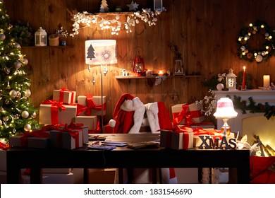 サンタクロースの衣装と帽子がテーブルの椅子にぶら下がっていて、メリークリスマスの装飾ギフトがクリスマスツリーと暖炉に光を当てて夜遅くに居心地の良いサンタホームワークショップのインテリアで休日の前夜にプレゼントします。