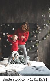 Mutter hält Baby 1-2 Jahre alt und trägt rote Strickpullover über Weihnachtsdekor im Zimmer. Winterferienzeit. Mutterschaft. Weihnachten.