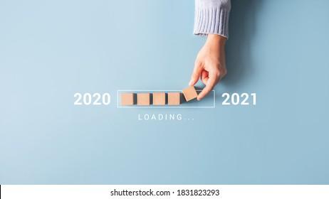 プログレスバーに木製の立方体を手で置いて、2020年から2021年までの新年をロードします。