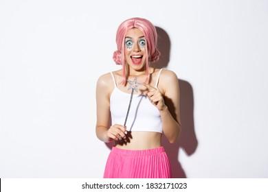Retrato de chica atractiva con peluca rosa y maquillaje brillante, vestida como un hada para la fiesta de Halloween, sosteniendo la varita mágica y sonriendo