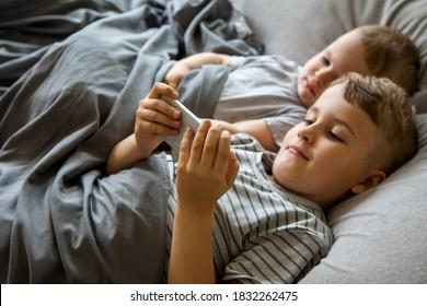 Twee kleine jongens met bruin haar liggen in een groot bed. Lach, kijk naar tekenfilms op de telefoon en tablet. Speel de gadget. Grijs beddengoed. Kinderen zijn blank.