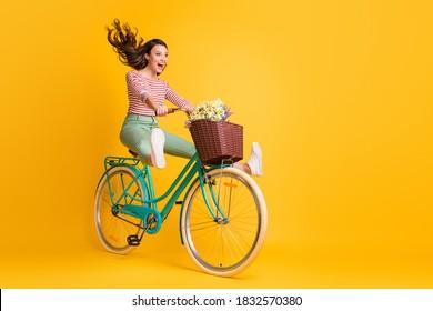 In voller Länge Körpergröße Foto von lustigen Mädchen schreien Reiten Fahrrad halten Beine hoch isoliert auf lebendigen gelben Farbe Hintergrund