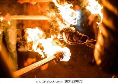 Flamme auf einer selbstgemachten Fackel, Feuer auf dem Hintergrund der Nachtstraßen, friedliche Aktionen mit Fackeln.