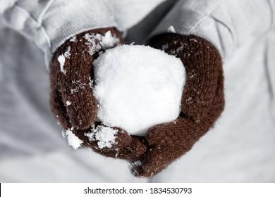 Handschoenen met een koude ijzige sneeuwbal, concept winter en grappige spelletjes met sneeuw, sneeuwballengevecht