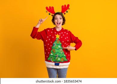 Foto von erstaunten positiven Mädchen Punkt Finger Hirsch Stirnband Weihnachten, Baum Dekor Pullover Weihnachten Noel Thema Party Geschenk isoliert über hellen Glanz Farbe Hintergrund