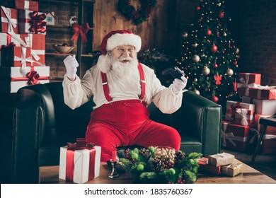 Aufgeregt süchtig grau Bart Santa Claus, sitzen Couch genießen Weihnachten Weihnachten Event spielen Videospiel gewinnen Erfolg erhöhen Fäuste tragen Mütze Kopfbedeckung im Haus drinnen Noel immergrünen Baum Ornament