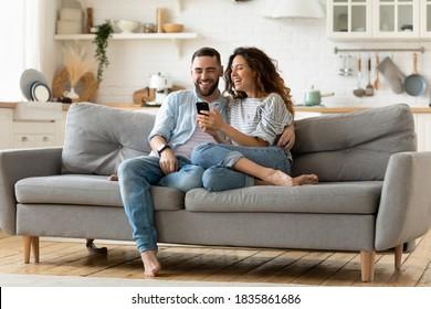 Glückliche junge Frau und Mann umarmen, Smartphone zusammen verwenden, sitzen auf gemütlicher Couch zu Hause, lächelnde überglückliche Frau und Ehemann, die Telefonbildschirm betrachten, sitzen auf Sofa im modernen Wohnzimmer