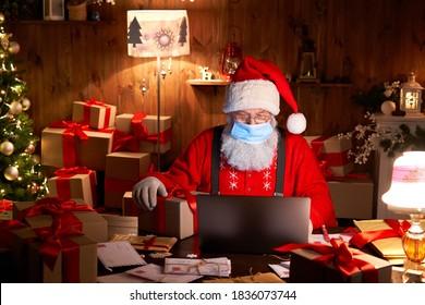 Viejo Papá Noel barbudo con mascarilla, sosteniendo la caja de regalo en la víspera de Navidad sentado en la acogedora mesa de casa tarde en la noche usando la computadora portátil Feliz Navidad Covid 19 concepto de distancia social del coronavirus.
