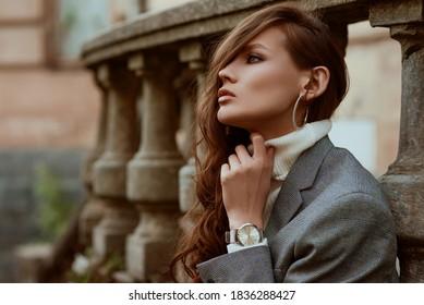 Straßenstil-Herbstporträt der eleganten modischen Frau, die trendige silberne Armbanduhr, karierten Blazer, weißen Rollkragenpullover, Creolen trägt, im Freien, in der Stadt posierend. Kopieren, leerer Platz für Text