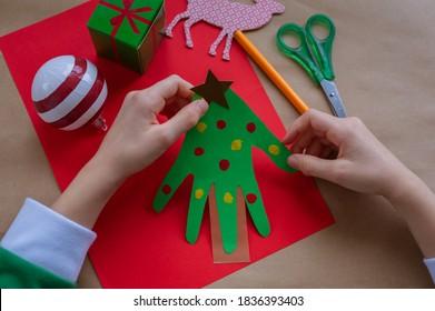 Wie man aus Papier einen Weihnachtsbaum für Glückwünsche und Spaß für Weihnachten macht. DIY-Konzept. Kinderhände basteln aus Papier. Schritt für Schritt Fotoanleitung.