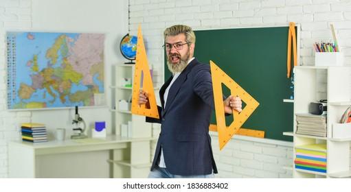 大学高校。テストの準備をします。先生のひげを生やした男の黒板の背景。先生の仕事。教室の講師。最終試験は口頭で書かれたものでも、実際的なものでもかまいません。理論を説明する先生。