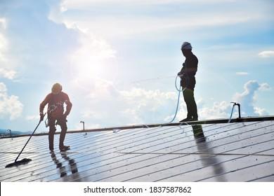 太陽光発電会社の労働者たちは、午後に屋根にほこりや鳩の糞で汚れた太陽電池パネルの表面を水で広げて洗っています。