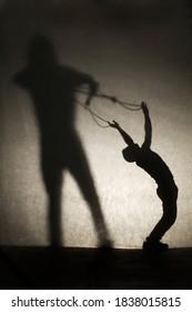 Sombra de silueta de mujer sosteniendo a un hombre como en un espectáculo de marionetas. Concepto de manipulación y dependencia / control. Idea de matrimonio / divorcio. Edición de película. Enfoque selectivo. Copie el espacio.