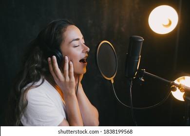 マイクで歌い、黒い壁と背景にランプのあるスタジオで声を録音する若い美しい女性。