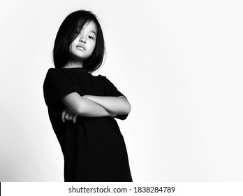 Black and white portrait of self-confident early adult asian kid girl in black t-shirt dress and bob hairstyle standing with her arms crossed at chest and looking down at camera