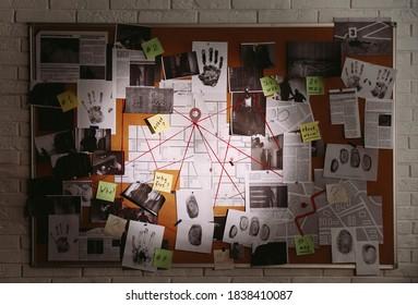 Detektivtafel mit Fingerabdrücken, Fotos, Karte und Hinweisen durch rote Schnur auf weißer Backsteinmauer verbunden