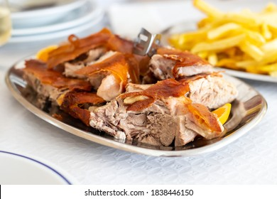 roasted pork with fried potato on dish on the table in restaurant