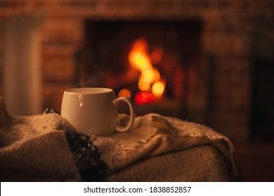 Mok met hete thee staande op een stoel met wollen deken in een gezellige woonkamer met open haard. Gezellige winterdag.