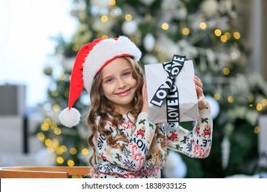 fröhliches Mädchen in Santa Red Hat mit Geschenkbox mit schwarzem Band Hintergrund Weihnachtsbaum. Weihnachtsgeschenke Konzept. Feier. Kind mit lockigem Haar und blauen Augen im Pullover. Einkaufen vor dem Urlaub