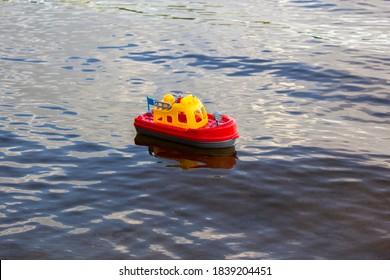 川に浮かぶおもちゃの船。鮮やかな赤と黄色のプラスチック製の船。おもちゃのハンドル。子供の水のおもちゃ。子供の海の旅の夢。自然の中で子供たちとのゲーム