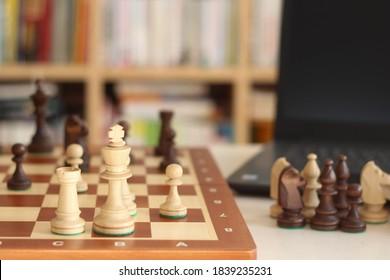 Speel online schaken. Schaken met laptop. Online onderwijs op afstand, communicatie met schaakcoach, familie. Thuisonderwijs. Games en deelnemen aan online schaaktoernooien. Kanaaltechnologie