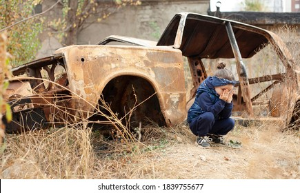 焦げた車の近くで小さな女の子が泣いています。ドネツクでの戦争。戦争ナゴルノカラバフ。燃え尽きた車。