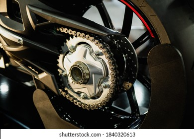 Detalle de una cadena trasera de motocicleta con tubos de escape. Vista trasera de una motocicleta con el foco en la cadena.