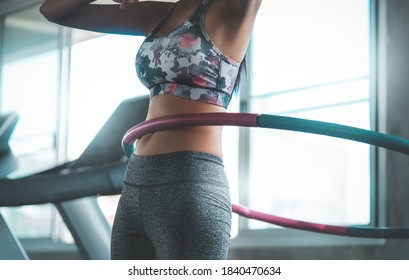 Sportliche Frau trainiert mit Hula Hoop im Fitnessstudio für ein gesundes Lifestyle-Konzept.