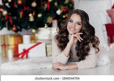 Glimlachende jonge vrouw met de doos van de Kerstmisgift dichtbij de kerstboom