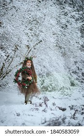 Fairy tale girl. Portrait a little girl in a deer dress with a painted face in the winter forest. Big brown antler. Fantasy girl with christmas wreath. Snowy park.