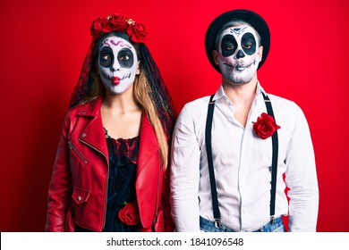 Couple wearing day of the dead costume over red making fish face with lips, crazy and comical gesture. funny expression.