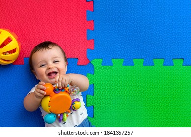 Funny baby playing on colorful eva rubber floor. Toddler having fun indoor his home. Top view.