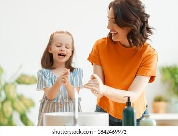 かわいい女の子と母親が手を洗っています。感染症やウイルスからの保護。